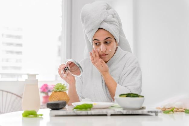 Vue de face femme appliquant la crème pour le visage