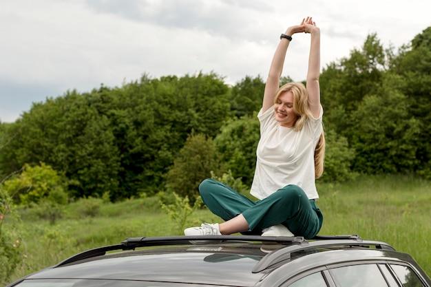 Vue de face femme appréciant la nature tout en posant sur le dessus de la voiture