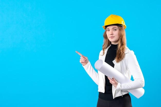 Vue de face femme architecte en casque jaune tenant plan sur bleu