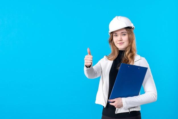 Vue de face femme architecte en casque tenant un plan de fichier bleu sur bleu