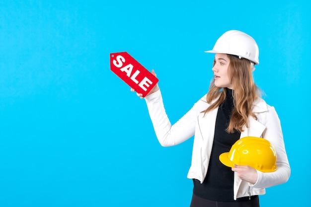 Vue de face femme architecte holding sale écrit sur bleu