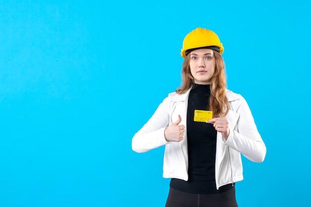 Vue de face femme architecte tenant une carte bancaire sur bleu