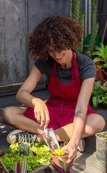 Vue de face femme assise tout en prenant soin des plantes