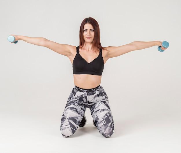 Vue de face de femme athlétique exerçant avec des poids