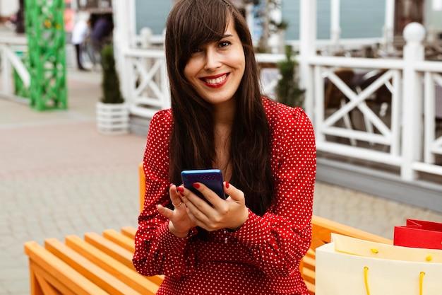Vue de face de la femme au centre commercial avec smartphone et sacs à provisions