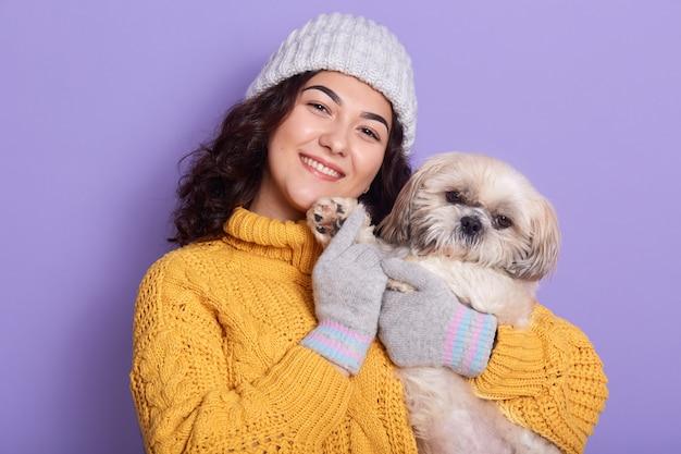 Vue de face de la femme aux cheveux noirs, porte un petit chien moelleux, jouant et passant du temps avec son animal préféré, se promener en plein air