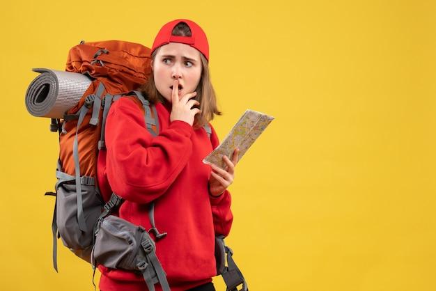 Vue de face femme backpacker tenant une carte de voyage regardant quelque chose