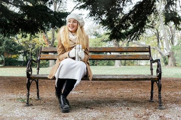 Vue de face de la femme sur le banc dans le parc en hiver