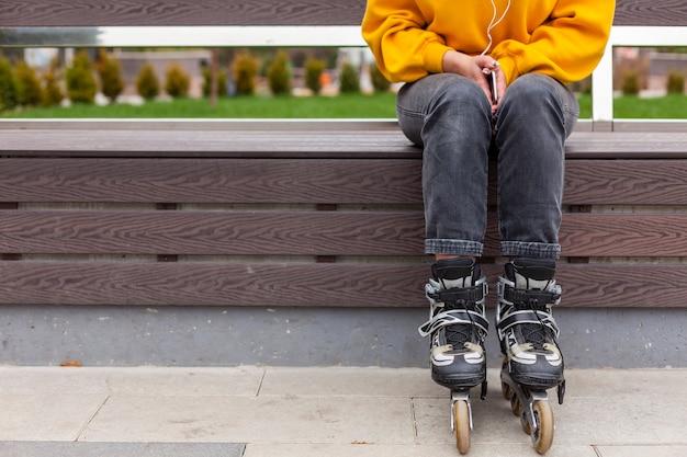 Vue de face d'une femme sur un banc portant des patins à roues alignées