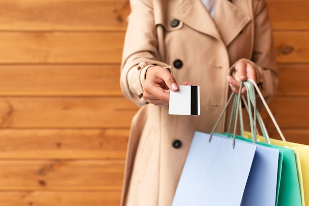 Vue de face de la femme avec beaucoup de sacs à provisions vous offrant sa carte de crédit