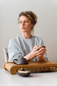 Vue de face d'une femme blonde aux cheveux bouclés, boire du thé et se détendre