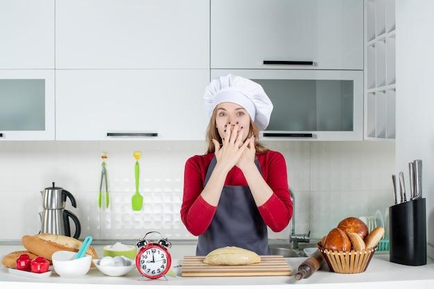 Vue de face femme blonde en chapeau de cuisinier et tablier mettant les mains sur son visage dans la cuisine