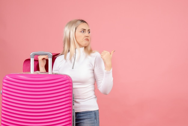 Vue de face femme blonde confuse debout près de valise en pointant sur quelque chose