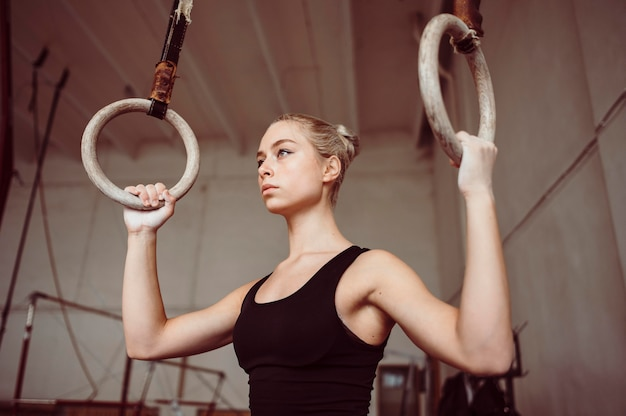 Vue de face femme blonde formation sur les anneaux de gymnastique