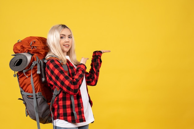 Vue de face femme blonde avec son sac à dos pointant avec les doigts derrière