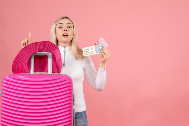 Vue de face femme blonde avec valise rose tenant le billet et la carte