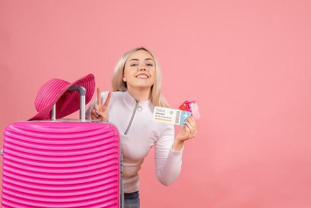 Vue de face femme blonde avec valise rose tenant le billet et la fabrication de cartes signe de la victoire