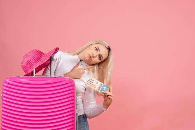 Vue de face femme blonde avec valise tenant billet d'avion