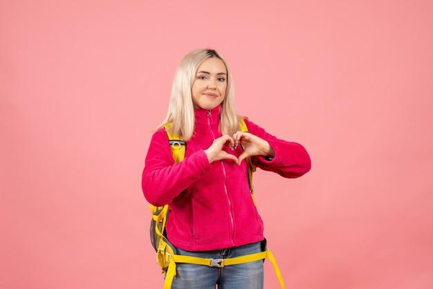 Vue de face femme blonde voyageur dans des vêtements décontractés faisant signe de coeur