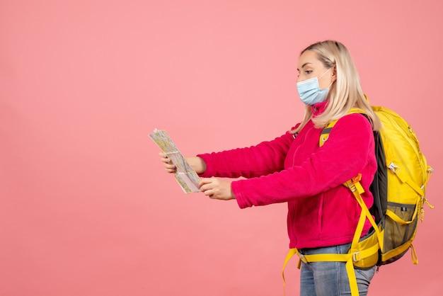 Vue de face femme blonde voyageur avec sac à dos jaune portant un masque en regardant la carte