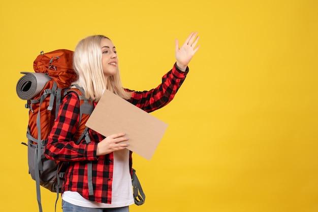Vue de face femme blonde voyageur avec son sac à dos tenant le carton saluant quelqu'un sur le mur jaune