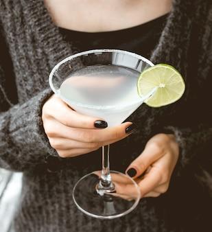 Vue de face une femme boit un cocktail rafraîchissant avec une tranche de citron vert