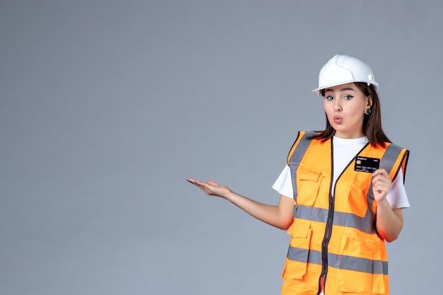 Vue de face d'une femme builder avec une carte bancaire noire dans ses mains sur un mur gris