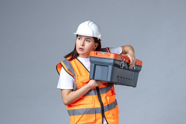 Vue de face d'une femme builder tenant une boîte à outils sur un mur gris