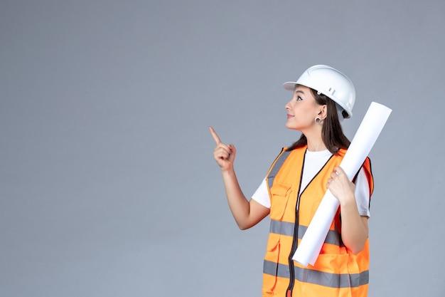 Vue de face d'une femme builder en uniforme avec une affiche dans ses mains sur un mur blanc