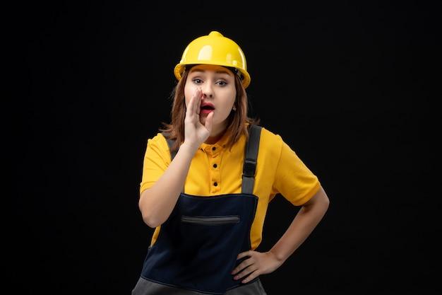 Vue de face femme builder en uniforme et casque chuchotant sur mur noir