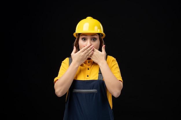 Vue de face femme builder en uniforme et casque surpris sur mur noir