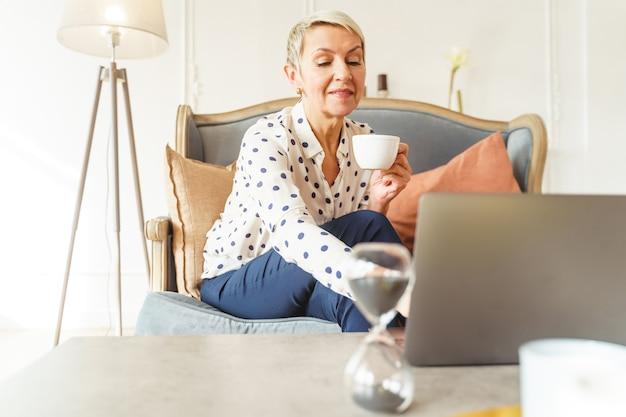 Vue de face d'une femme caucasienne âgée souriante et élégante assise devant son ordinateur