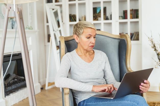 Vue de face d'une femme caucasienne senior ciblée avec un ordinateur portable assis dans un fauteuil