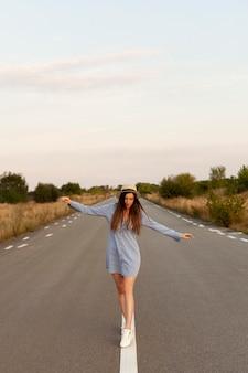 Vue de face de la femme avec chapeau posant au milieu de la route avec les bras ouverts