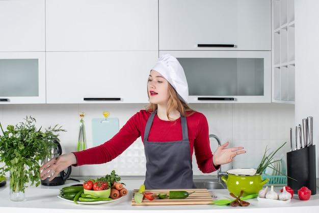 Vue de face femme chef en chapeau de cuisinier atteignant la main aux verts