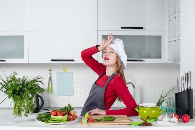 Vue de face femme chef en chapeau de cuisinier debout avec pose spéciale