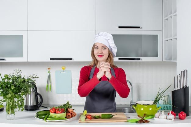 Vue de face femme chef en chapeau de cuisinier main dans la main