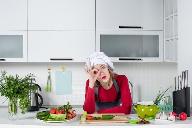 Vue de face femme chef en chapeau de cuisinier mettant un signe okey devant son œil