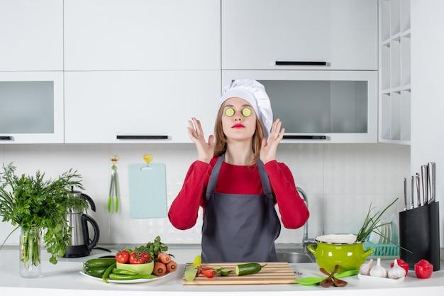 Vue de face femme chef en chapeau de cuisinier mettant des tranches de concombre sur ses yeux dans la cuisine