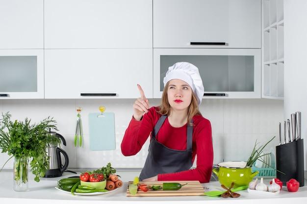 Vue de face femme chef en chapeau de cuisinier pointant quelque chose du doigt