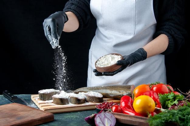 Vue de face femme chef couvrant des tranches de poisson cru avec de la farine légumes frais sur planche de bois bol à farine couteau sur table de cuisine