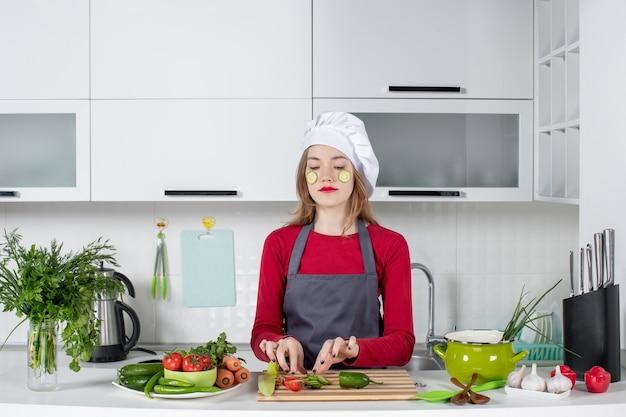 Vue de face femme chef occupée en chapeau de cuisinier mettant des tranches de concombre sur son visage