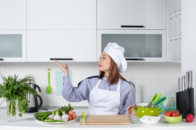 Vue de face d'une femme chef positive et de légumes frais pointant quelque chose sur le côté droit dans la cuisine blanche