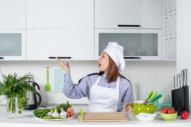 Vue de face d'une femme chef surprise et de légumes frais pointant quelque chose sur le côté droit dans la cuisine blanche