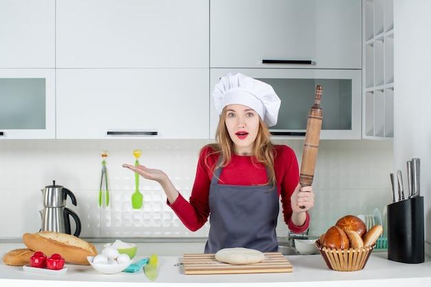 Vue de face femme confuse en chapeau de cuisinier et tablier tenant un rouleau à pâtisserie dans la cuisine