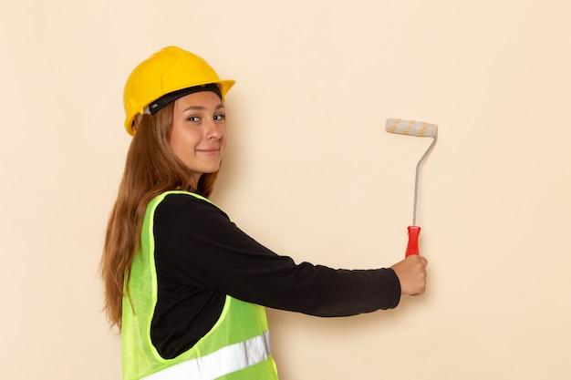 Vue de face femme constructeur en casque jaune chemise noire peinture murs sur le mur blanc