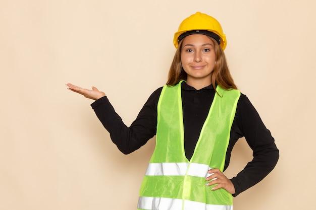 Vue de face femme constructeur en chemise noire casque jaune posant et souriant sur le mur blanc