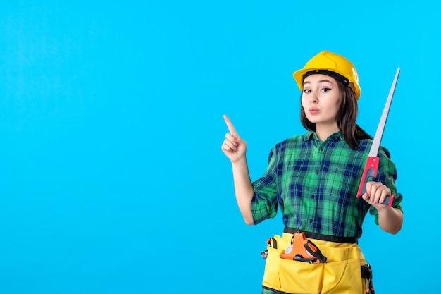 Vue de face femme constructeur tenant une petite scie