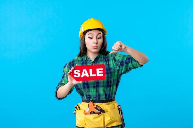 Vue de face femme constructeur tenant vente rouge écrit sur bleu