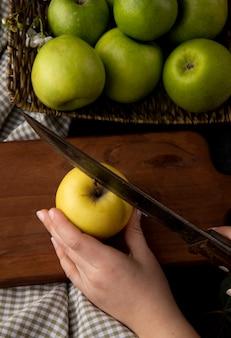 Vue de face femme coupe la pomme jaune sur une planche avec des pommes vertes dans un panier sur une nappe à carreaux sur une table